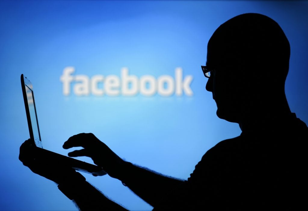 A man is silhouetted against a video screen with an Facebook logo as he poses with an Dell laptop in this photo illustration taken in the central Bosnian town of Zenica, August 14, 2013. REUTERS/Dado Ruvic (BOSNIA AND HERZEGOVINA - Tags: BUSINESS TELECOMS) - RTX12L6I facebook İçin kritik süreç başlıyor! Facebook İçin Kritik Süreç Başlıyor! RTX12L6IFB 1024x701